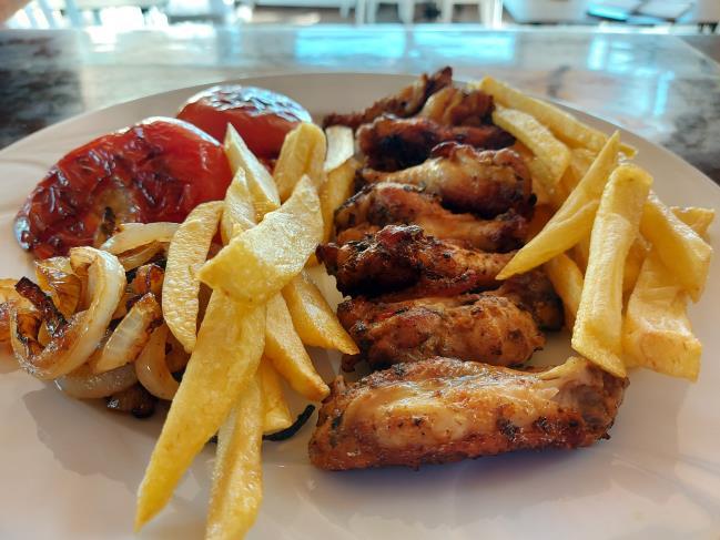 Tavuk kanat, ızgara domates, ızgara soğan, ve patates kızartması