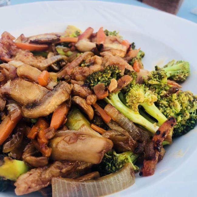 Wok tavasında, jülyen kesilmiş soya soslu piliç budu, soğan, sarımsak, zencefil, brokoli, mantar, havuç ve özel karışmlar